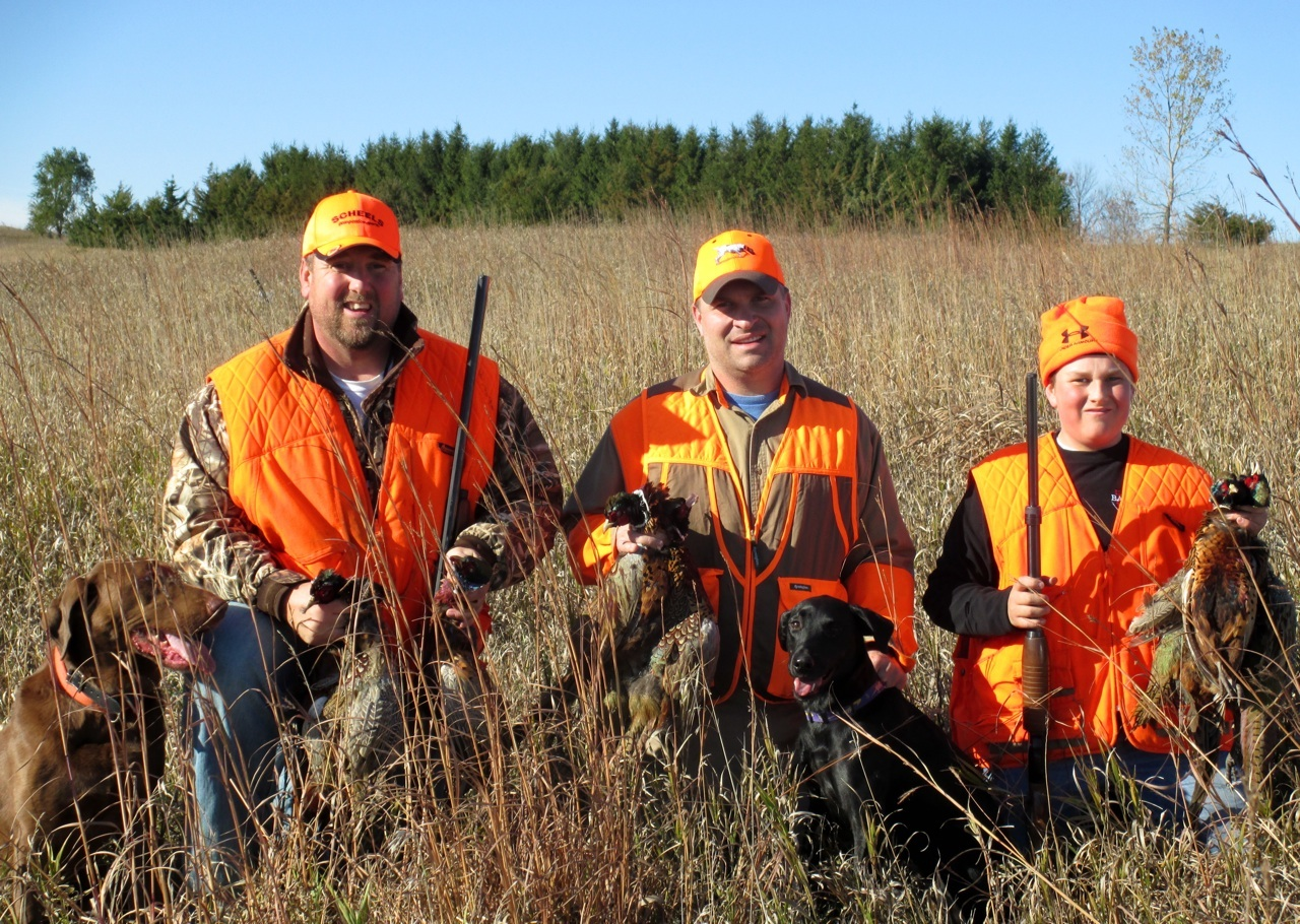 (photo by Steve Weisman) L to R - The author's son-in-law, son and grandson hold their three-person limit on last Saturday's pheasant opener.