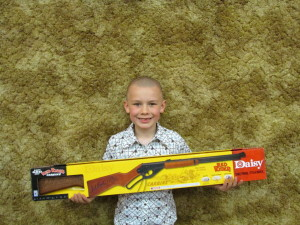 7 year old Logan Jensen of Moville IA  proudly displays the Red Ryder BB Gun he won at the 2014 Oak Ridge Gobblers Hunting Heritage Banquet.