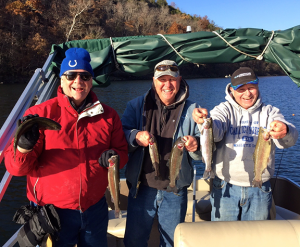 (photo by Mark Devore) (L to R) John Amick, Bill Elling and the author hold six nice trout during their trip to Lake Taneycomo.