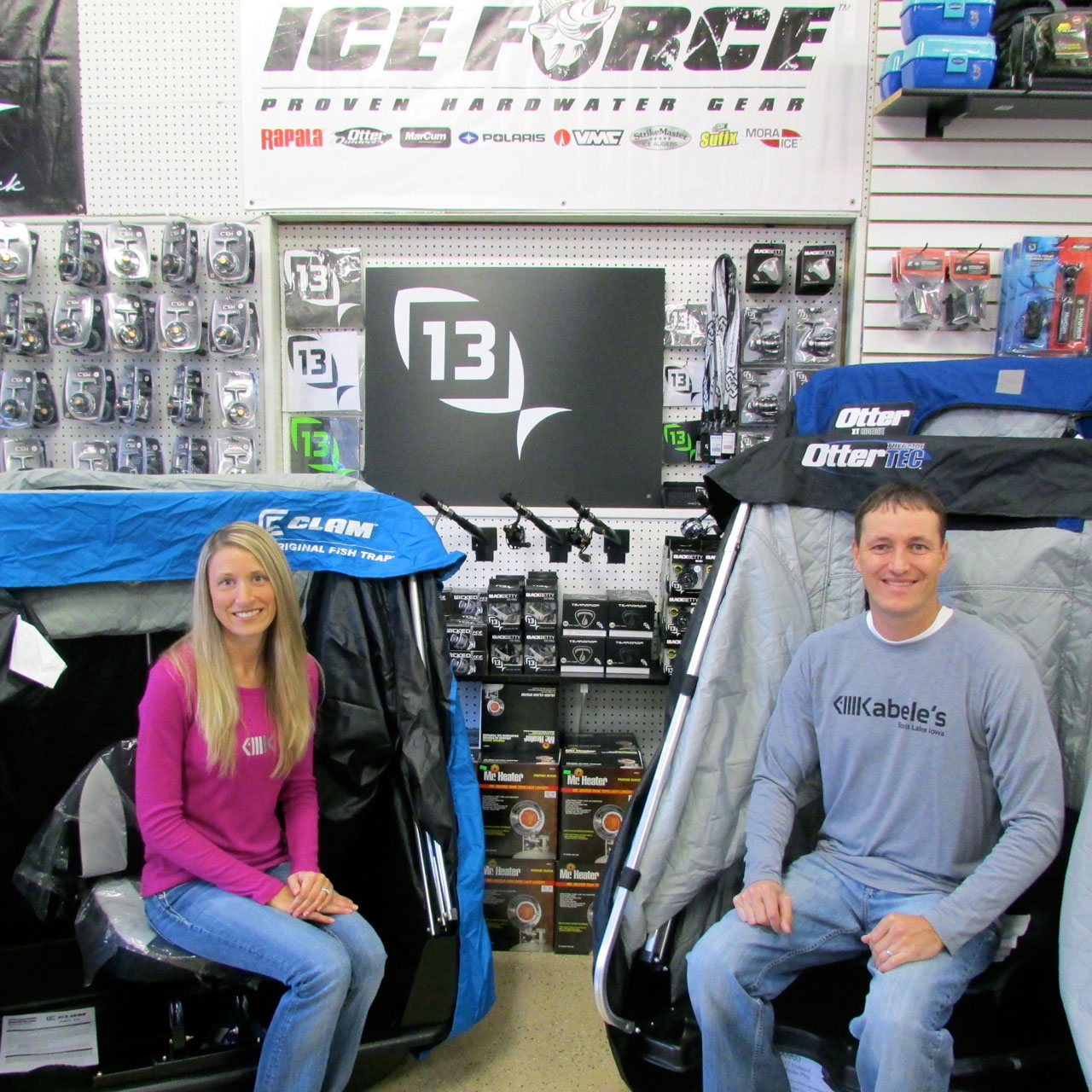 (photo by Steve Weisman) All set and ready to go. Surrounded by all kinds of ice fishing products, Tanya and Thane Johnson test out a couple of single-person portable shelters.