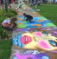 Adults and kids enjoyed decorating the drab sidewalks with colorful artwork.