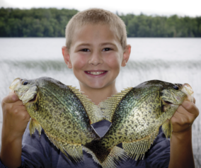 Kyle Thompson from Milford, IA holding up a pair of pre-spawn crappies.  (Photo by Rocky Thompson)