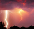 Fork lightning over dark orange sky on stormy day