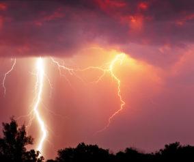 Fork lightning over dark orange sky on stormy day